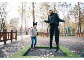 妈妈和女儿一起在秋季公园的蹦床上跳_7560347