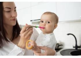 妈妈用勺子喂可爱的宝宝_9696738