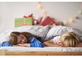 孩子们在圣诞节睡在舒适的床上_11727976