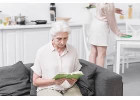 家中坐在沙发上看书的老年妇女_2698350