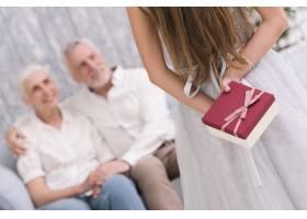 小女孩背着礼物坐在沙发上的祖父母面前_4929763