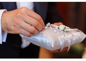 带结婚戒指的枕头新郎在仪式上拿戒指_3337197