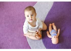 可爱可爱的小妇人抱着洋娃娃坐在紫色地毯上_9028784