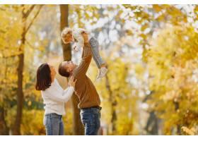 可爱时髦的一家人在秋天的田野里玩耍_7724930