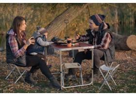 可爱的一家人坐在森林里野餐_7169711