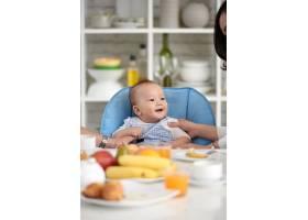 可爱的亚洲宝宝与家人坐在餐桌前_5577376