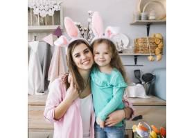 可爱的女孩和戴着兔子耳朵的母亲拥抱着_3817260
