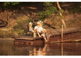 可爱的小女孩和她们的爷爷在湖边或河边钓鱼_13457470