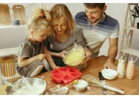 可爱的小女孩和她漂亮的父母在家里的厨房里_12699590
