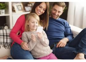 可爱的小女孩父母在家里玩手机_11100969