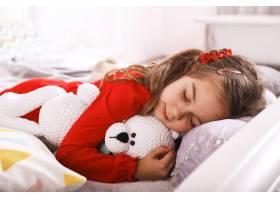 可爱的小女孩穿着红色睡衣带着一个白熊玩具_7250335