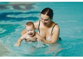 可爱的小男婴母亲和儿子一家人在水里玩_11183385