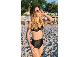 夏日海滩上一位穿着黑色泳衣的年轻漂亮女子_12965051