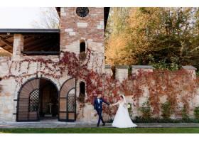 在温暖的秋日幸福的新郎和新娘手牵着手走_7497164