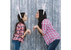 在灰色木质背景下女儿和母亲摆出兔子般的_3978593