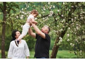 在祖父手中快乐的一对夫妇和孙女在户外享_9694473