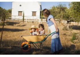 坐在手推车里的两个拿着红苹果的姐妹被女人_3143459