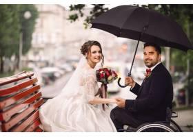 坐在轮椅上的新娘和新郎坐在公园的长凳上接_2612616