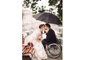 坐在轮椅上的新娘和新郎坐在公园的长凳上接_2612619