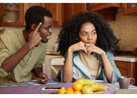 夫妻争执不下恼怒的黑皮肤美女坐在厨房餐_9437628