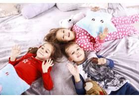 三个快乐的孩子穿着睡衣躺在毯子上_7250331