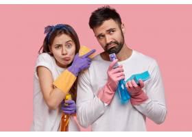 不高兴的女人和男人拿着喷雾海绵穿着白_11408491