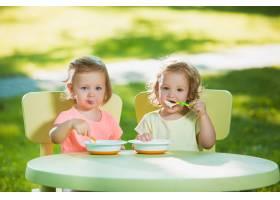 两个小女孩坐在一张桌子旁一起在绿色的草_8049765