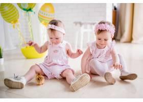 两个穿着粉色连衣裙的小女孩在工作室的地板_2631504