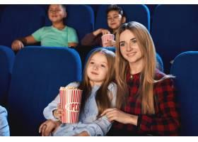 全家人在电影院共度时光的前景迷人的年轻_10101823