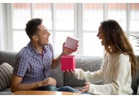 兴奋的年轻男子打开礼盒接受妻子的礼物_3953855