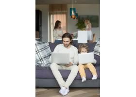 儿子模仿父亲在家里坐在沙发上拿着笔记本电_3938159