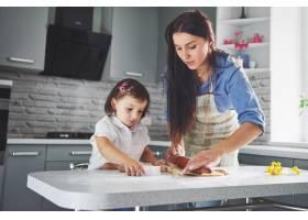 一个漂亮的女儿和她的母亲在厨房做饭_9146729