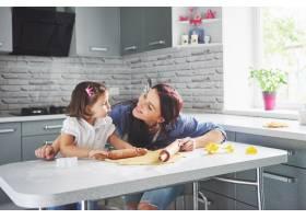 一个漂亮的女儿和她的母亲在厨房做饭_9146774
