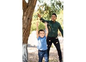 一位年轻人和他的儿子在森林里玩耍和扔干树_13006195