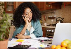 一位忧伤的非洲黑人女子坐在厨房里的笔记本_9534800