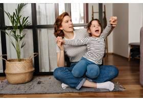 一位身穿条纹t恤的红发女子抱着女儿坐在客_12677760