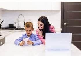 一名年轻女子在家里使用笔记本电脑工作而_8472467