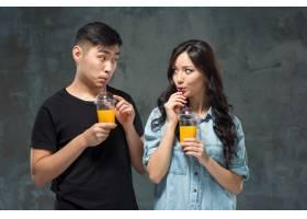 一对年轻漂亮的亚洲夫妇喝着一杯橙汁_8364517