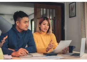 一对年轻的亚洲夫妇在管理财务使用笔记本_3521664