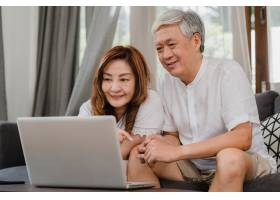 一对亚洲高年级夫妇在家中使用笔记本电脑_5820748