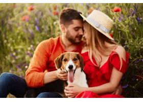 一男一女和一只有趣的小猎犬坐在绿色的田野_2914014