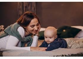 母亲带着她的男婴庆祝圣诞节_11981334