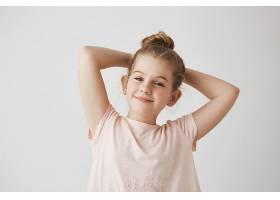 甜美的金发女孩穿着粉色T恤梳着发髻手_8685947