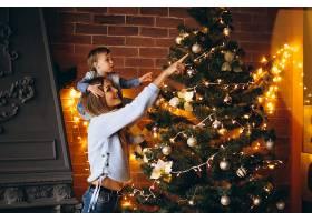 母亲带着小女儿装饰圣诞树_3655471