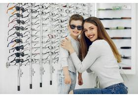 母亲带着年幼的儿子在眼镜店里_5011160