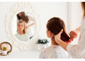 母亲在家里给女儿扎头发的背影_5098284