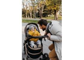 爸爸和孩子坐在户外的婴儿车里_11904682