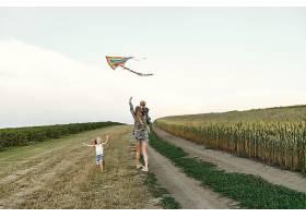 母亲带着可爱的小孩子在夏天的田野里_5252081