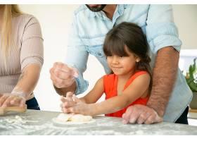 爸爸教女儿如何在厨房桌子上用面粉做面团_9649204