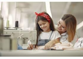 母亲带着年幼的女儿在工厂缝制衣服_6632284
